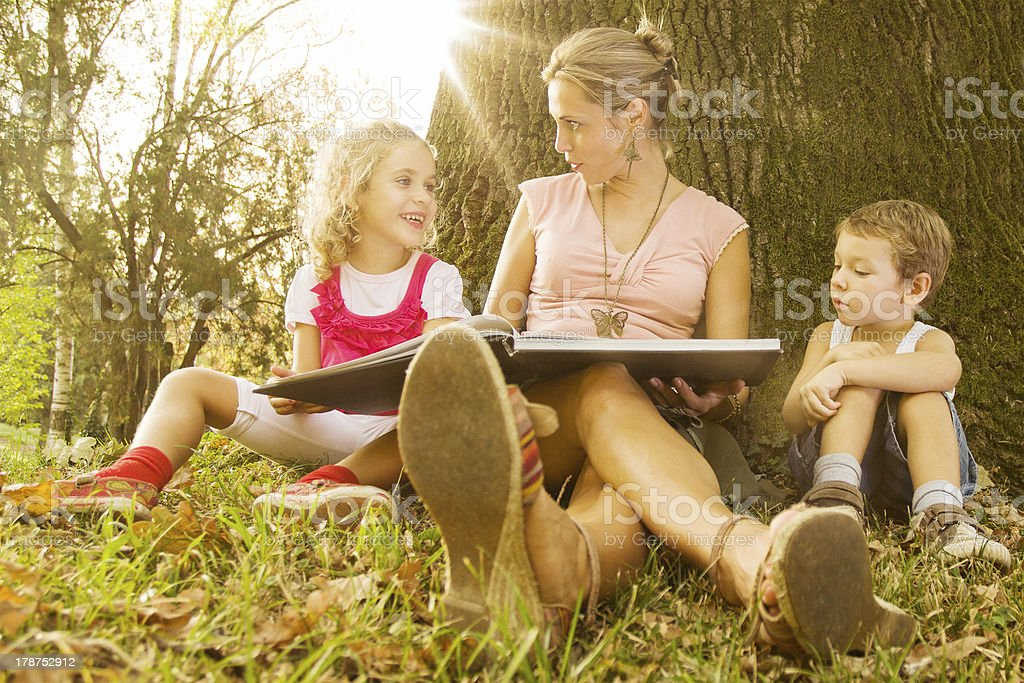 A young mother reading to her two children outside stock photo