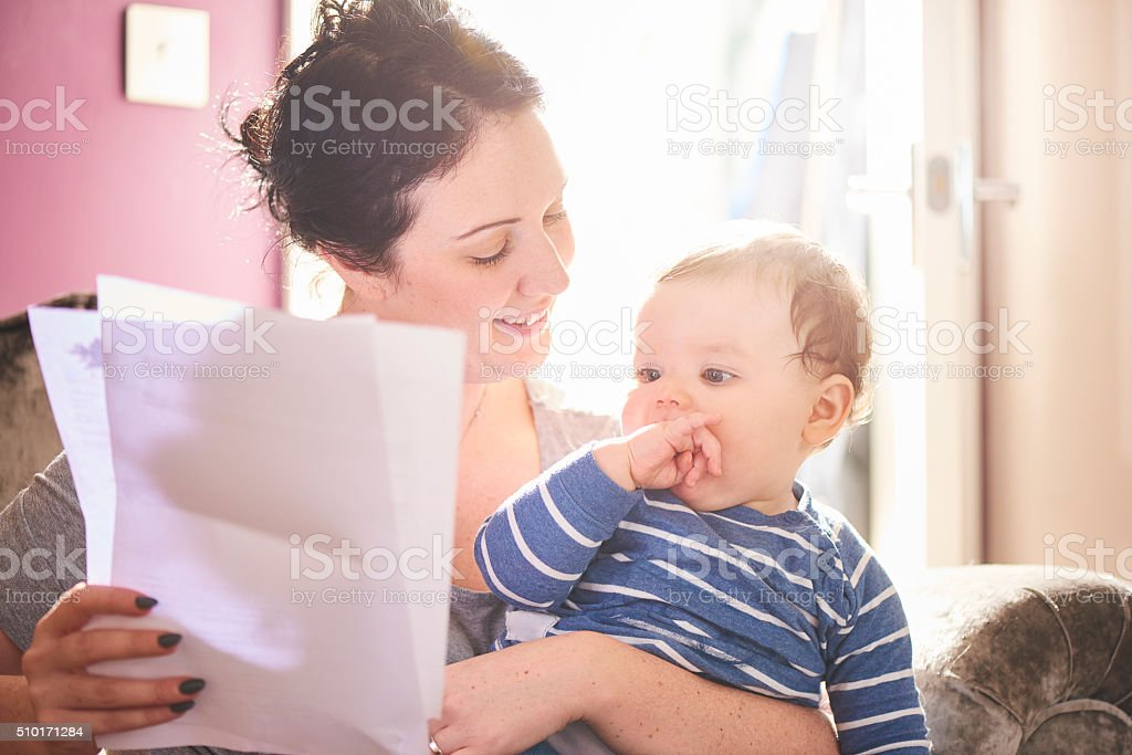 young mother reads through mortgage agreement stock photo
