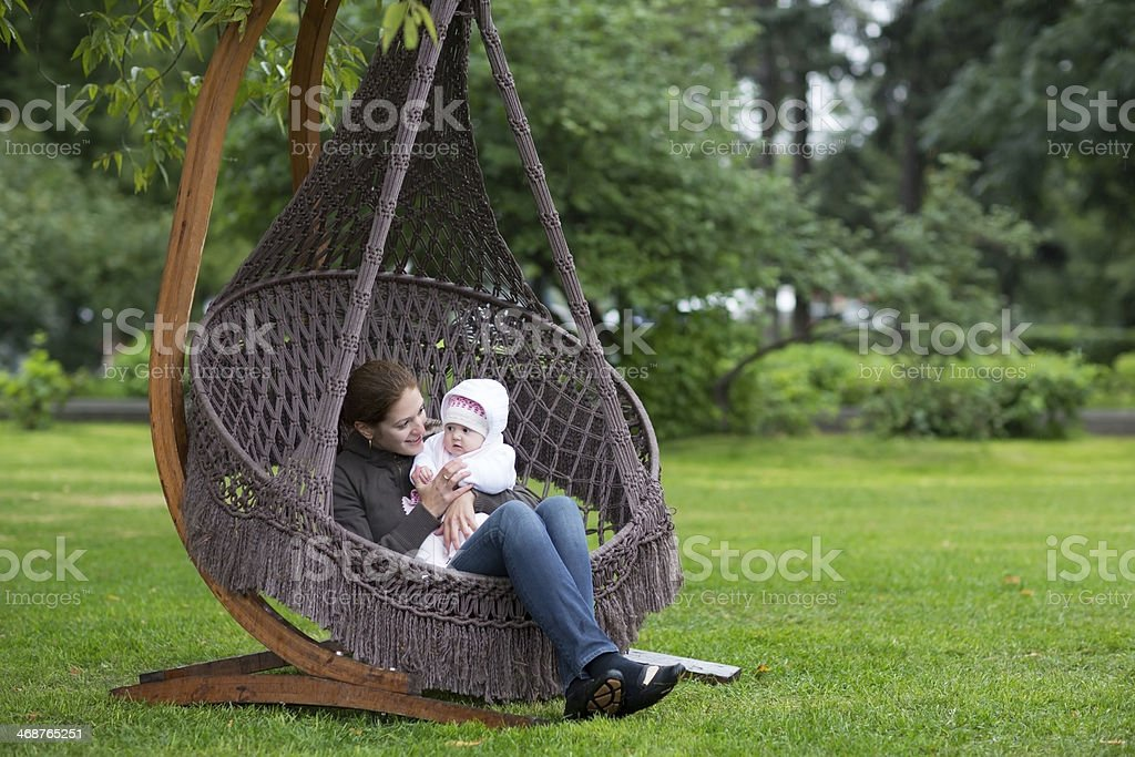 Young mother relaxing with a baby girl in hammock royalty-free stock photo