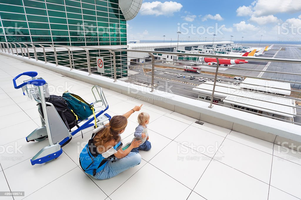 Young mother show to baby boy airplanes in airport stock photo