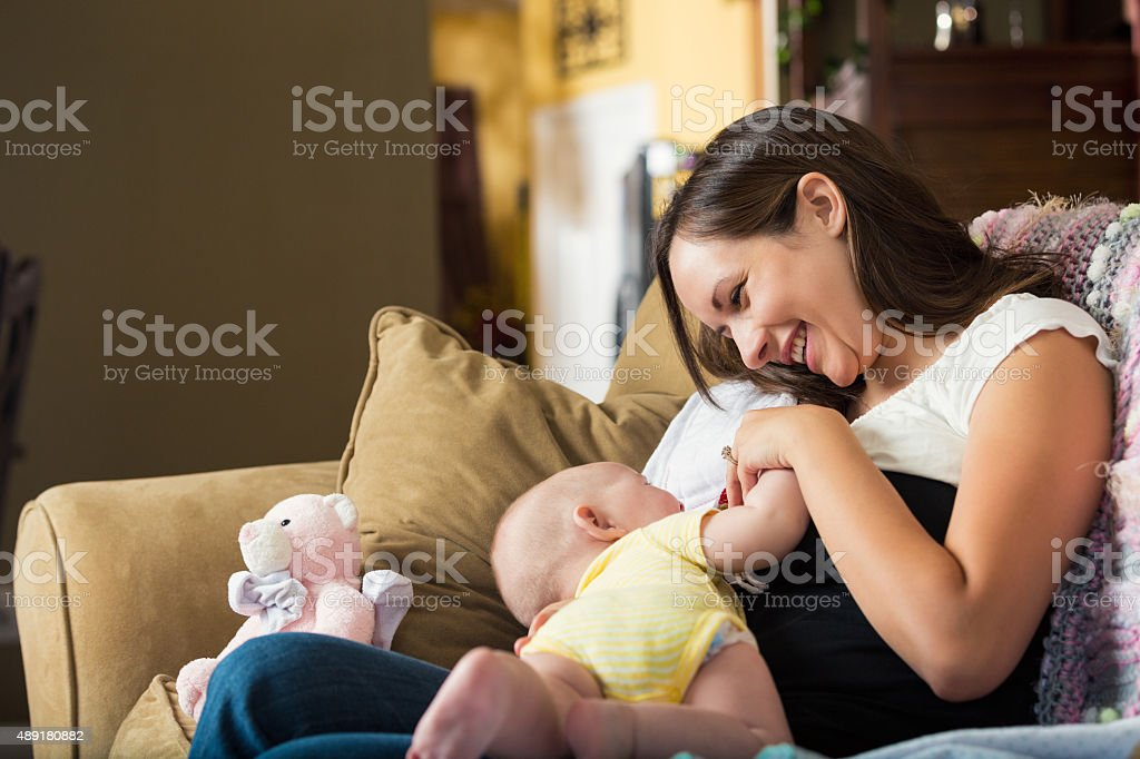Young mother smiling while breastfeeding daughter at home stock photo