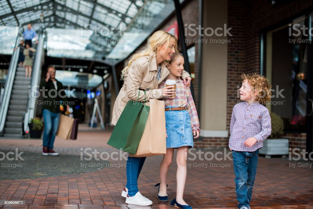 young mother talking with her little kids during shopping at shopping centre stock photo