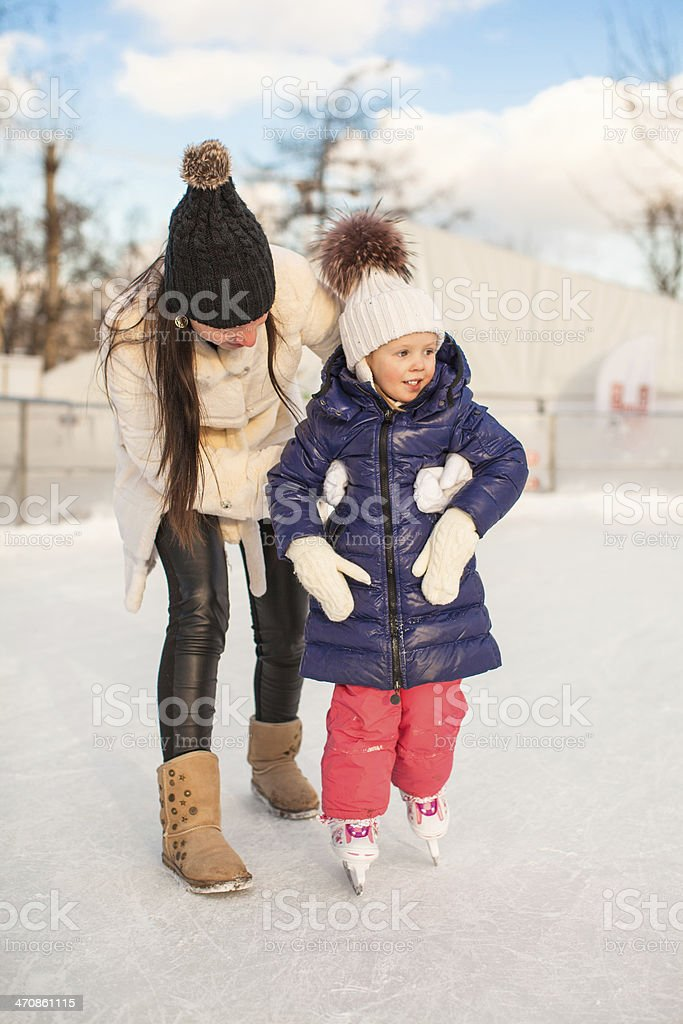 Young mother teaching her little daughter to skate on ice-rink stock photo