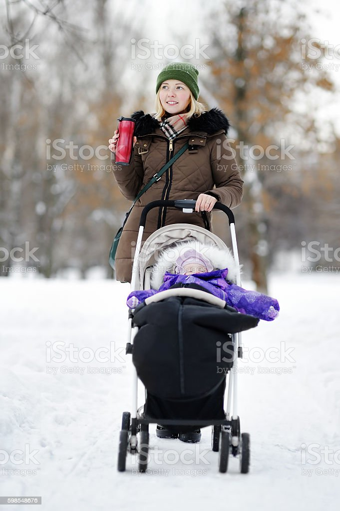 Young mother walking with baby in stroller stock photo