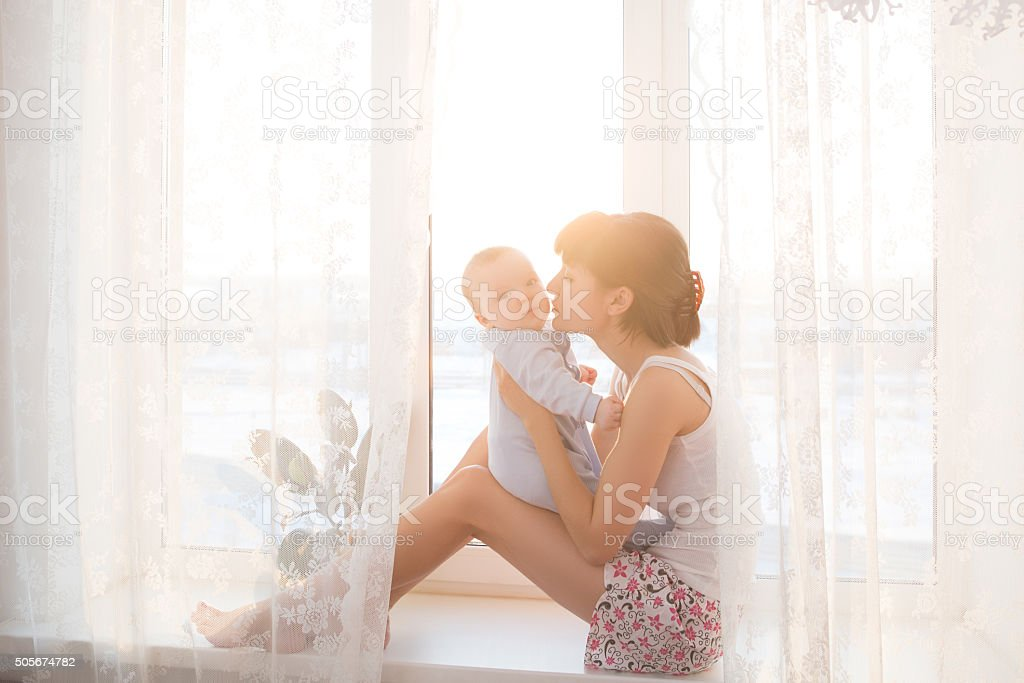 Young mother with a baby in beautiful bedroom stock photo
