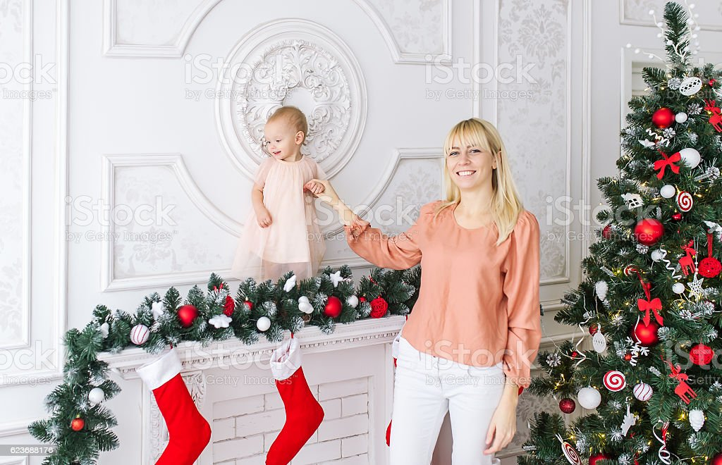 Young mother with baby girl in front of xmas tree stock photo