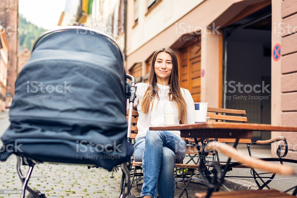 Young mother with baby stroller having coffee at a cafe stock photo