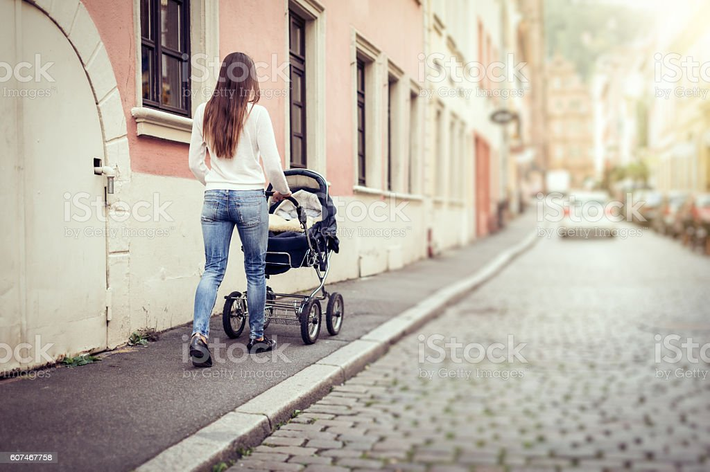 Young mother with baby stroller in the city stock photo