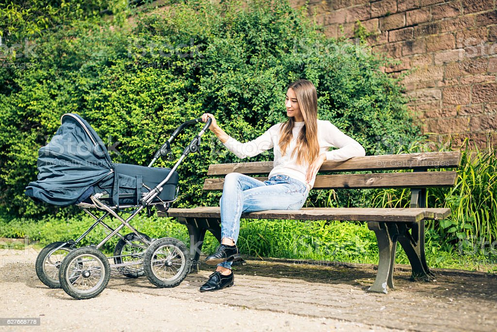 Young mother with baby stroller in the park stock photo