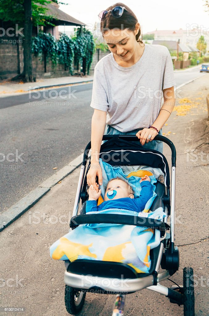 Young mother with child in pram stock photo