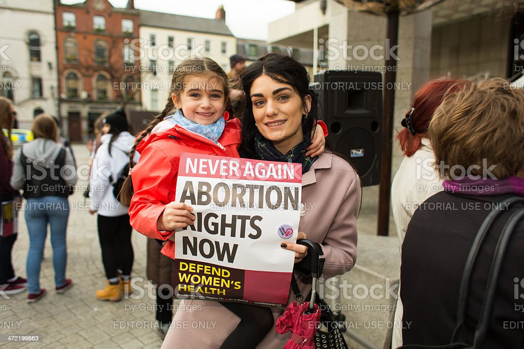 Young mother with daughter holding together poster regarding abortion rights stock photo