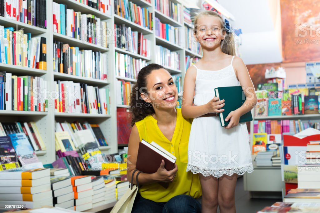 young mother with daughter in book shop stock photo