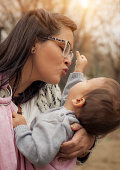 Young mother with her baby boy in baby carrier scarf
