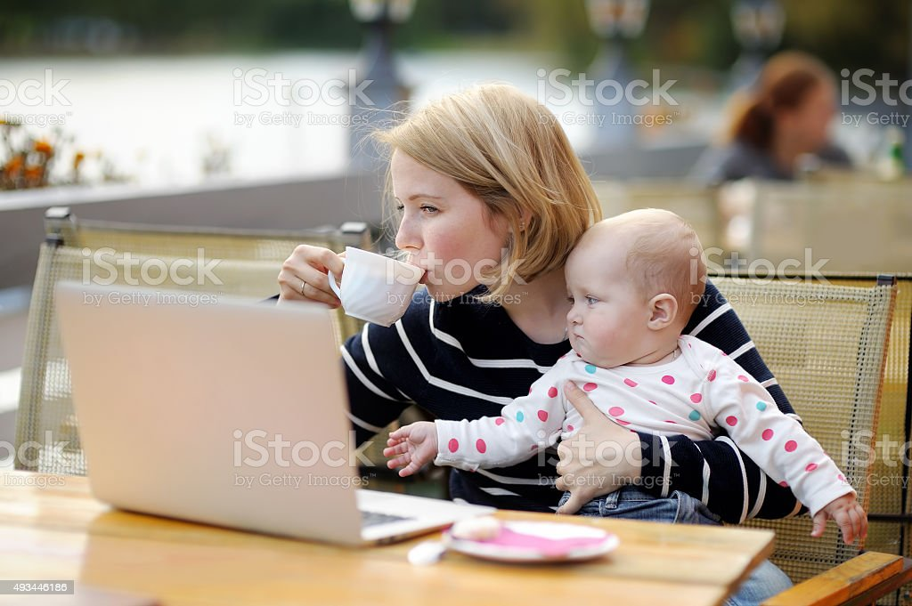 Young mother with her baby working or studying on laptop stock photo