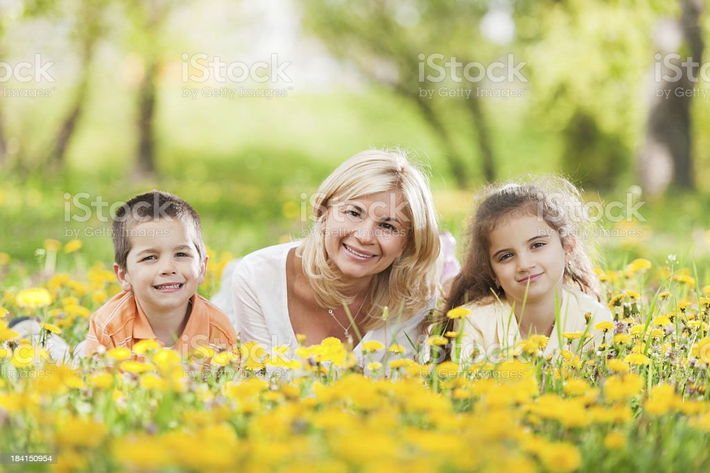 Young mother with her children lying down among the flowers. royalty-free stock photo