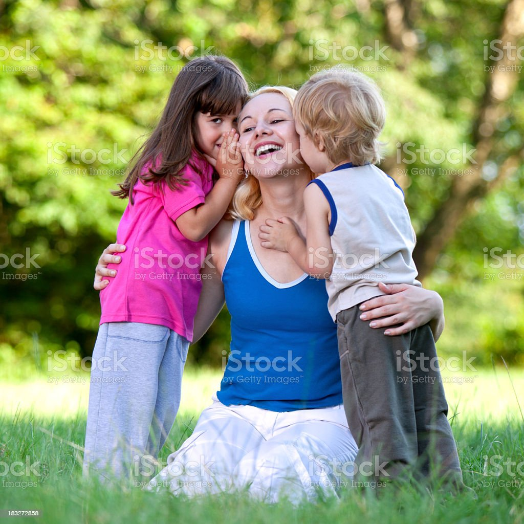 Young mother with two children playing outdoors in the park royalty-free stock photo