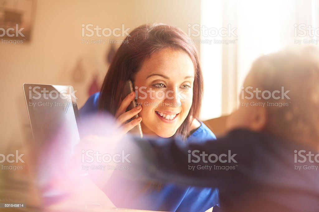 Young mother working from home with toddler stock photo