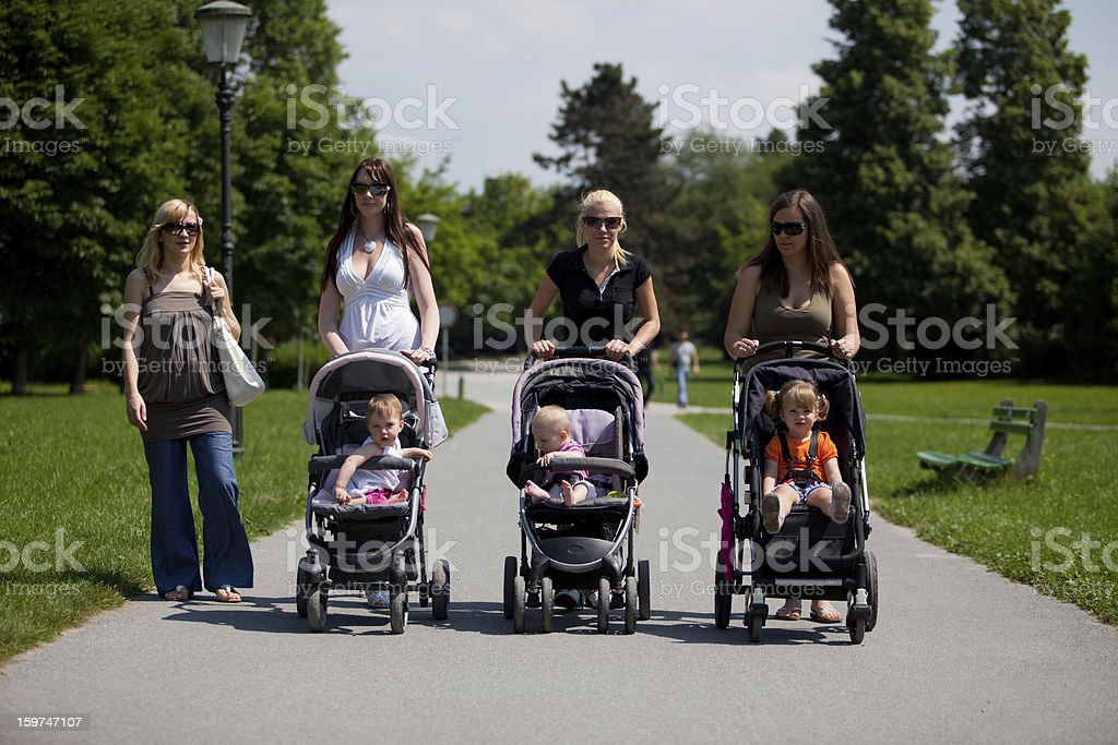 Young mothers in a park walking their babies royalty-free stock photo