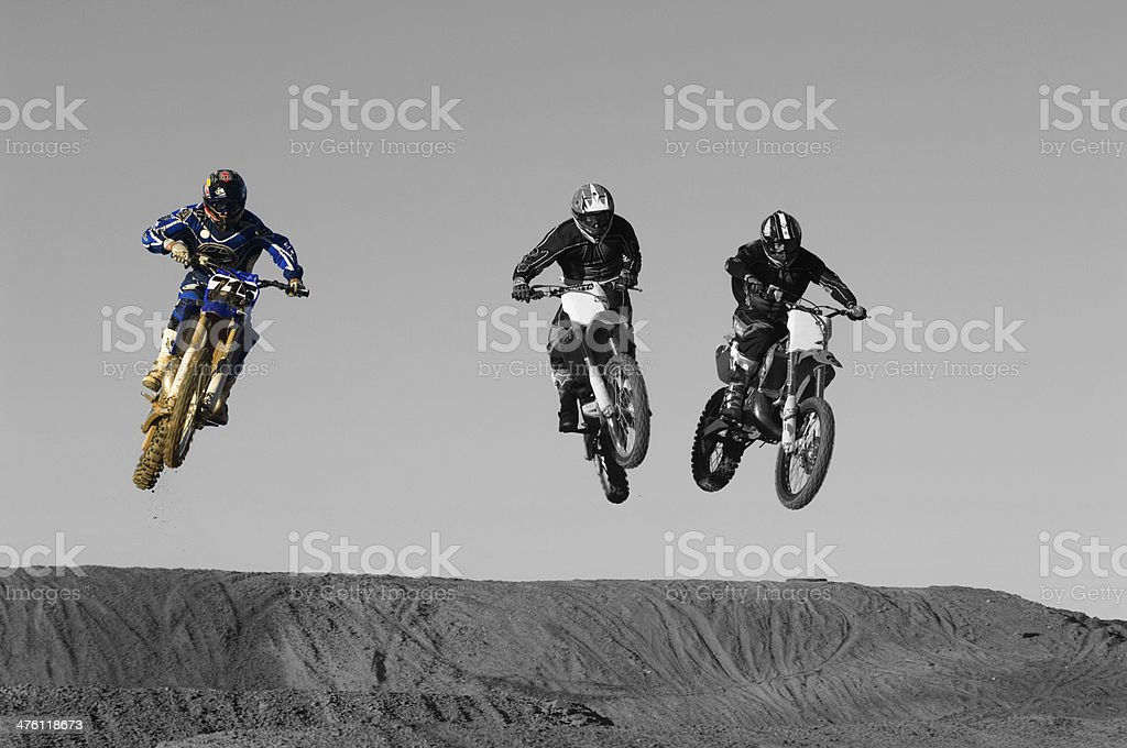 Young motocross racers riding on dirt track stock photo