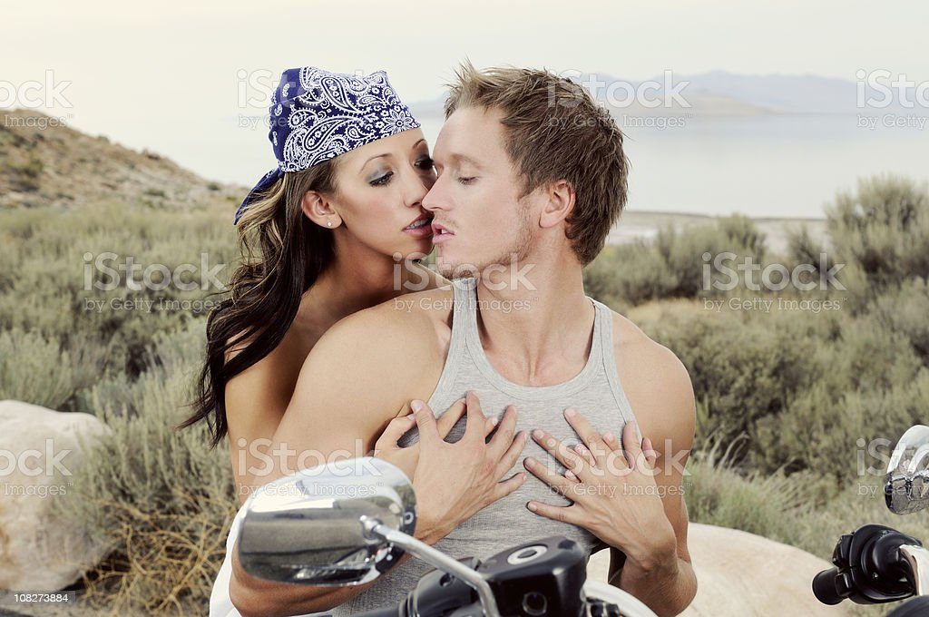 Young Motorcycle Couple Sharing A Passion Filled Moment In Time stock photo