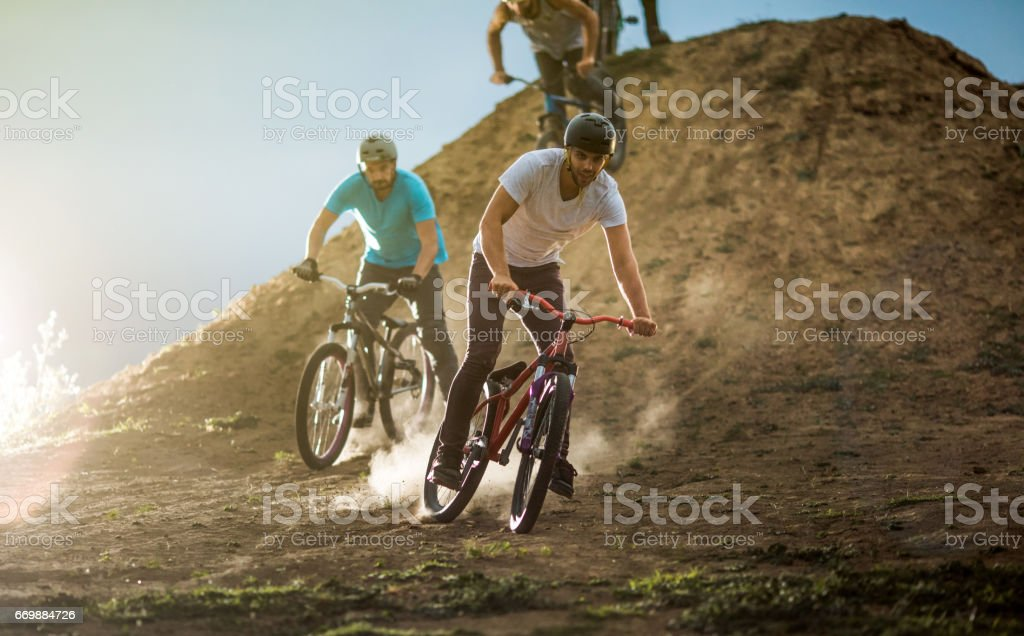Young mountain bike cyclists racing on dirt road. stock photo