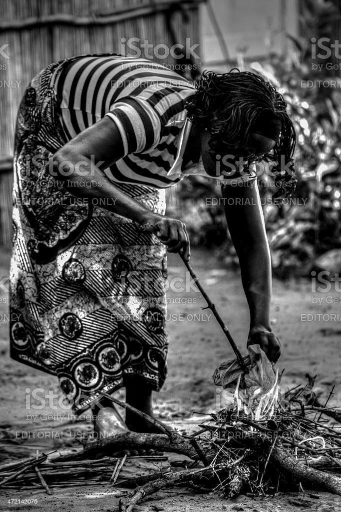 Young Mozambican woman starts fire stock photo