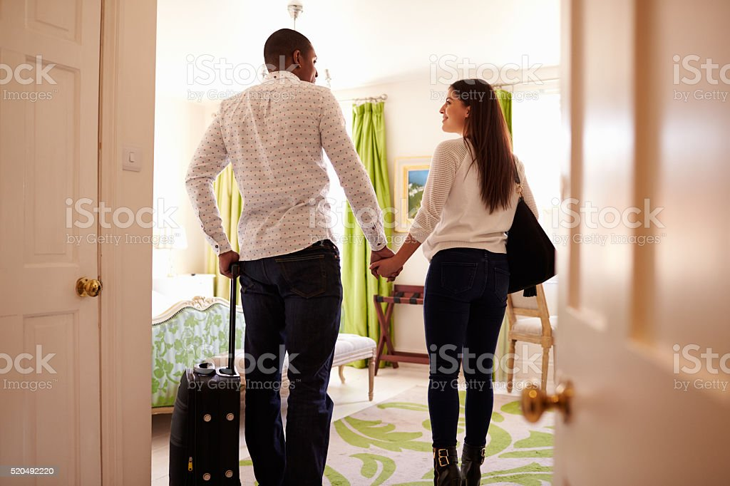 Young multi ethnic couple walk in to a hotel room, stock photo