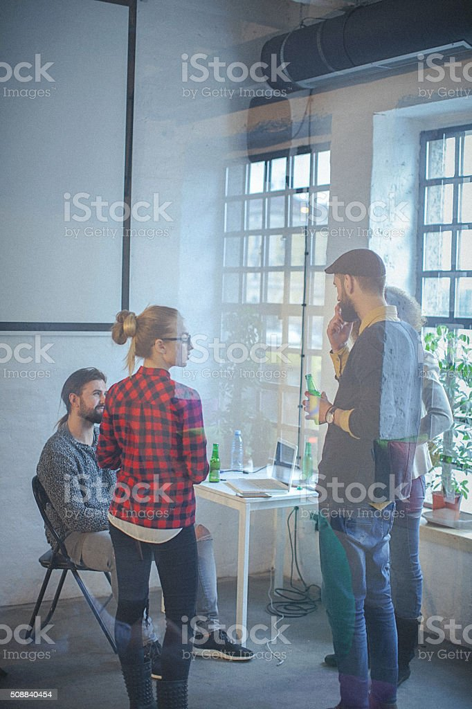 Young multicultural group enjoying happy hour at modern office space stock photo