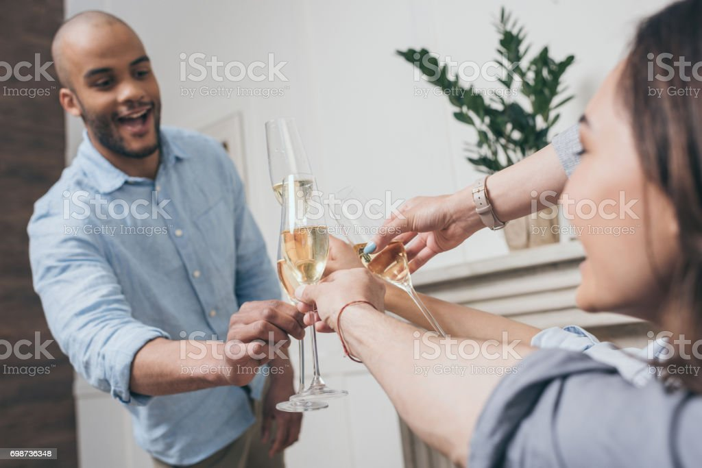 young multiethnic friends clinking with glasses of champagne at home stock photo