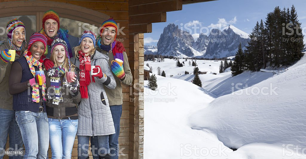 Young multi-ethnic people celebrating under cabin roof in snowy mountains royalty-free stock photo