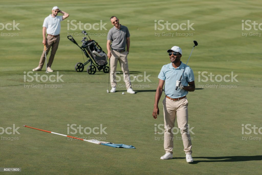 young multiethnic sportsmen standing with golf clubs on green pitch stock photo