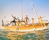 Young multiracial happy friends jumping from sailing party boat