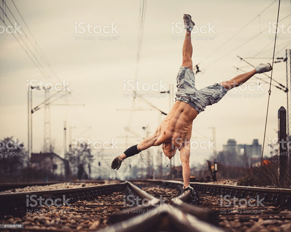 Young muscle man on railroad tracks stock photo