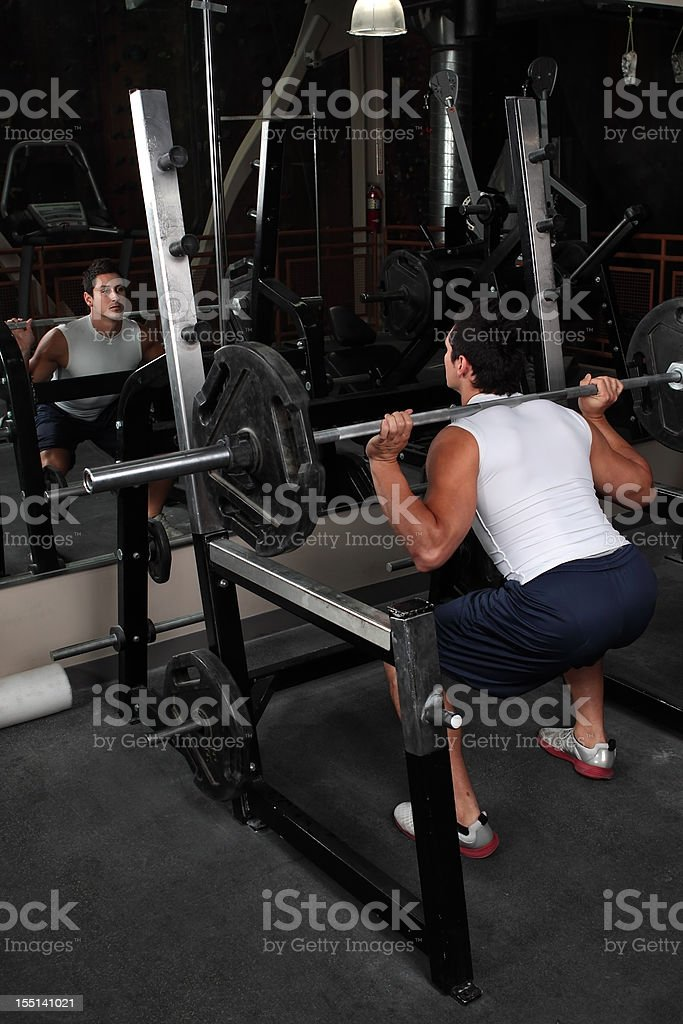 Young, muscular male lifting weights in front of mirror royalty-free stock photo