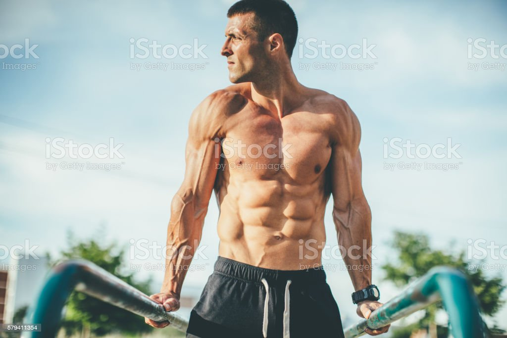 young muscular man doing triceps exercise outdoors stock photo