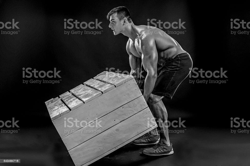 Young Muscular man flipping box stock photo