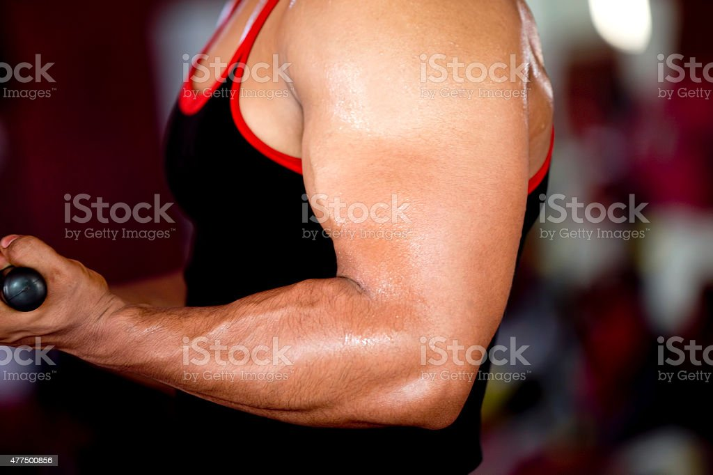 Young muscular man hand lifting in a gym stock photo