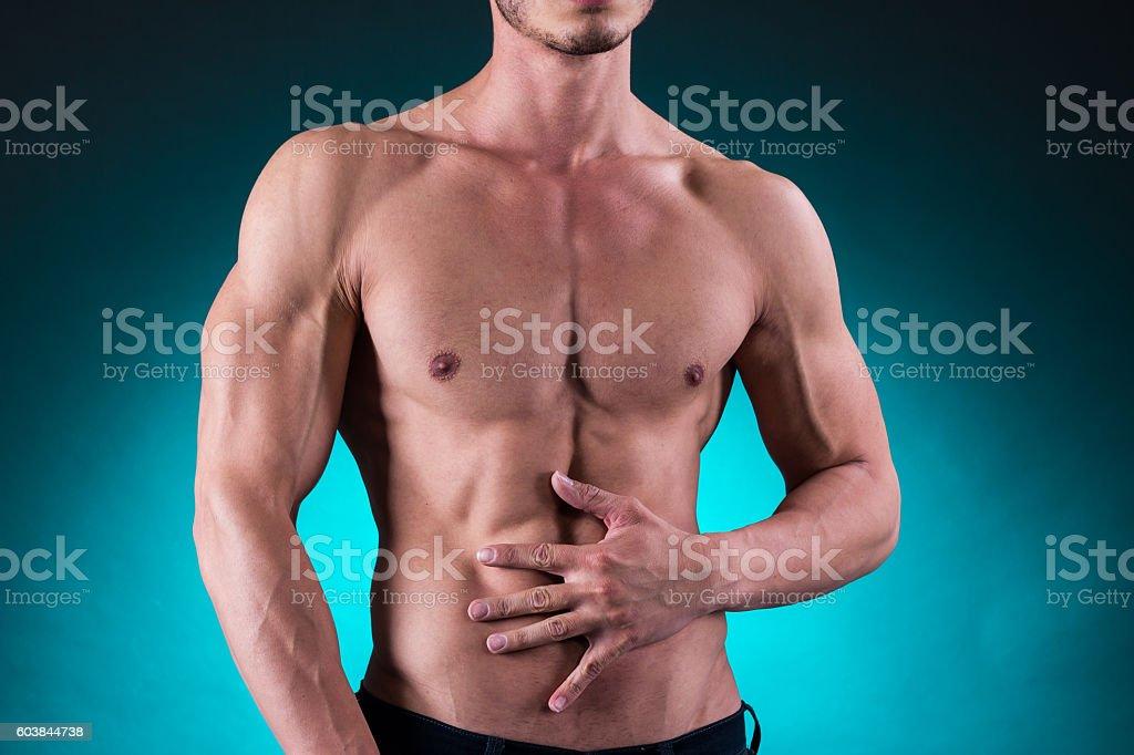 Young muscular man having abdominal pain stock photo