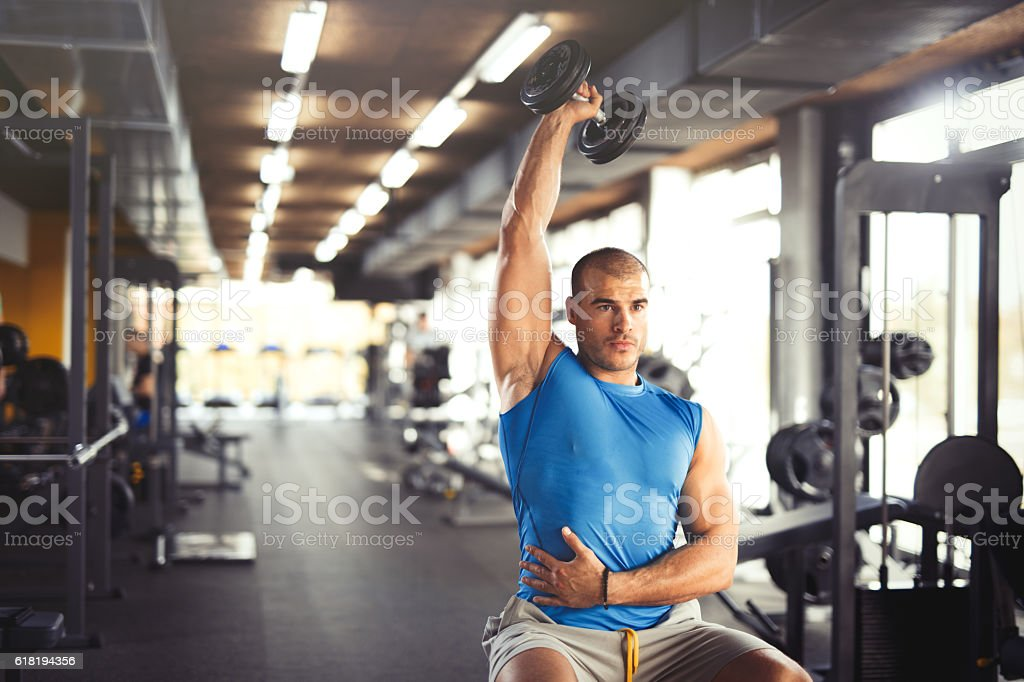 Young muscular man lifting up dumbbells at the gym. stock photo
