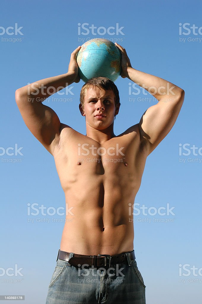 Young muscular man playing with a terrestrial globe royalty-free stock photo