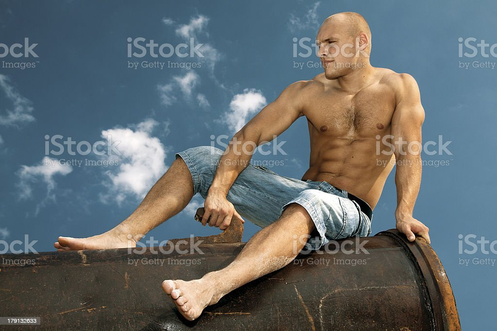 Young muscular man sitting on sky background royalty-free stock photo