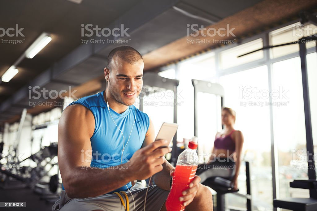Young muscular man using mobile phone at the gym. stock photo