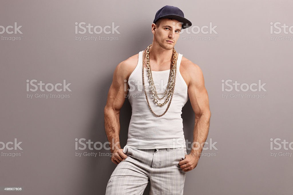 Young muscular rapper leaning on a wall stock photo
