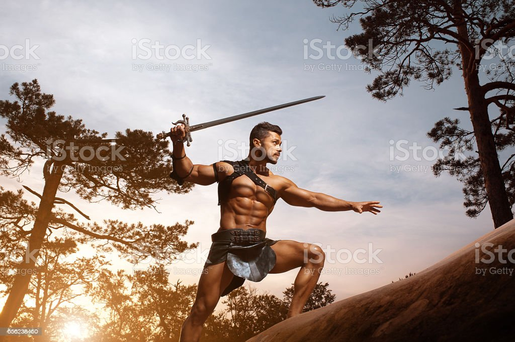 Young muscular warrior with a sword at the mountains stock photo