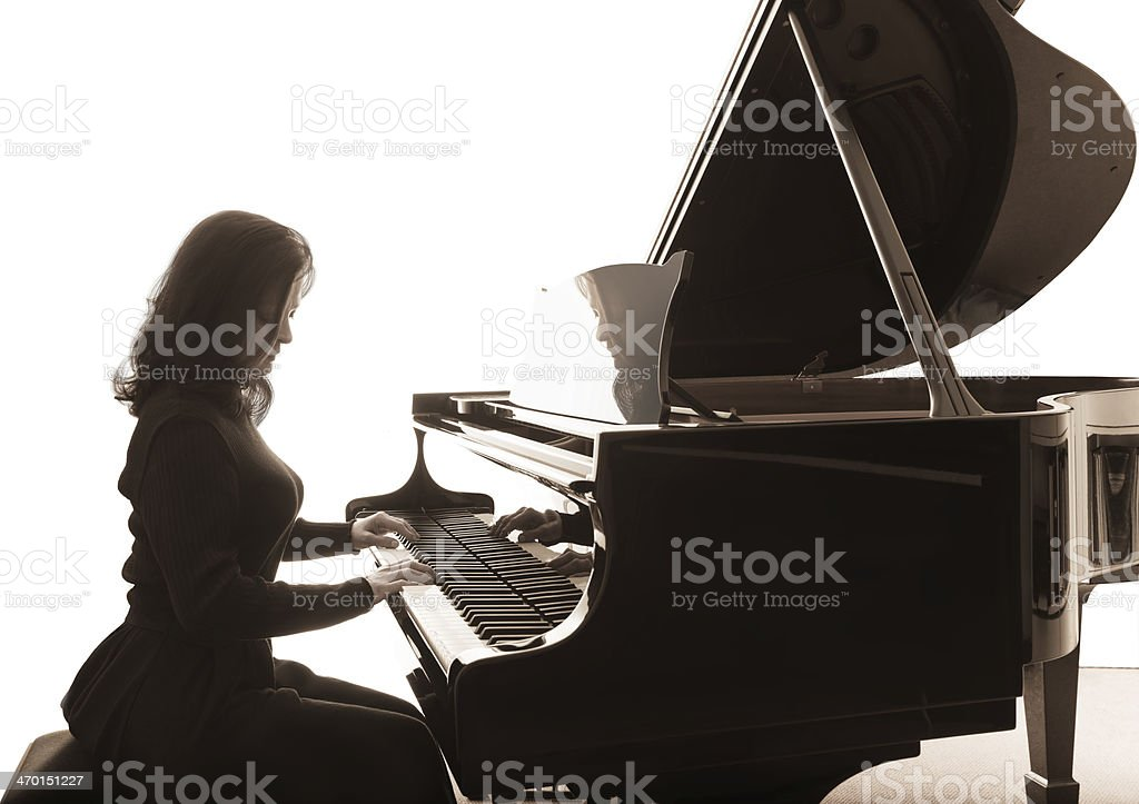 Young musician plays the grand piano stock photo