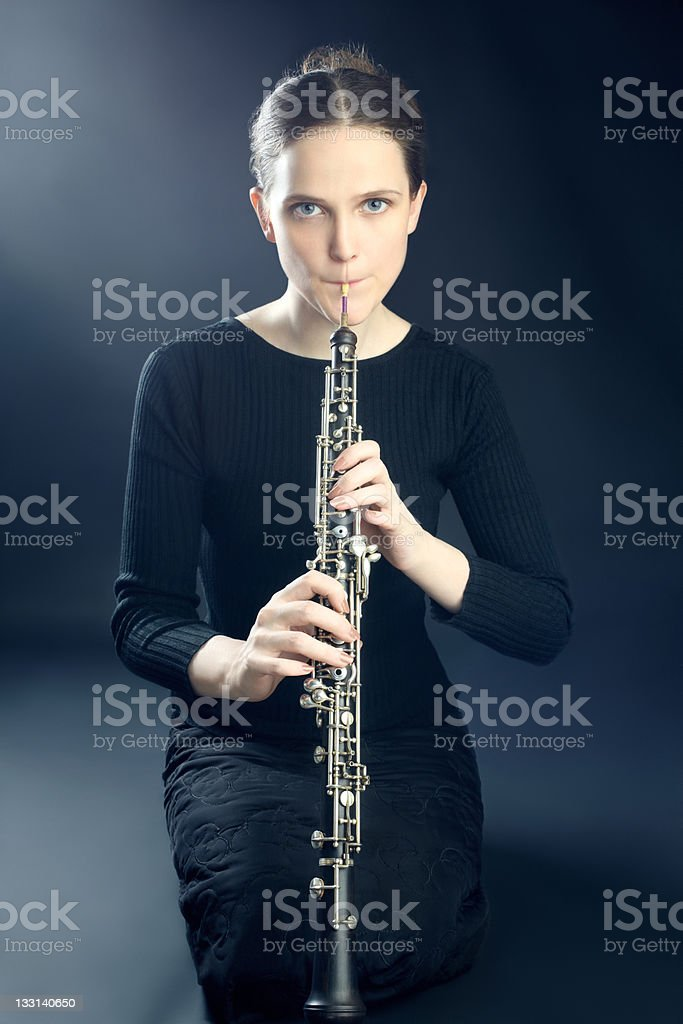 Young musician woman playing oboe musical instrument stock photo