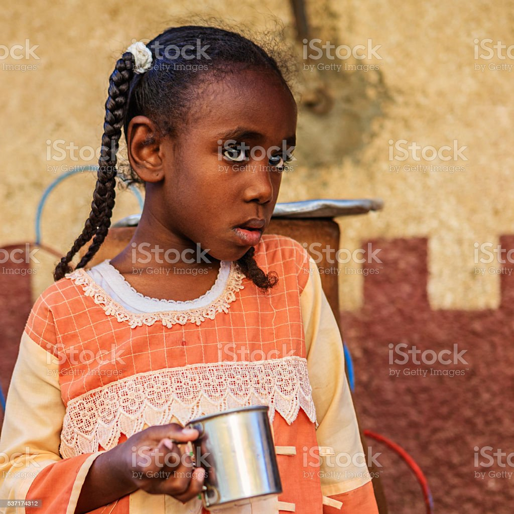 Young Muslim girl drinking water from well in Southern Egypt stock photo