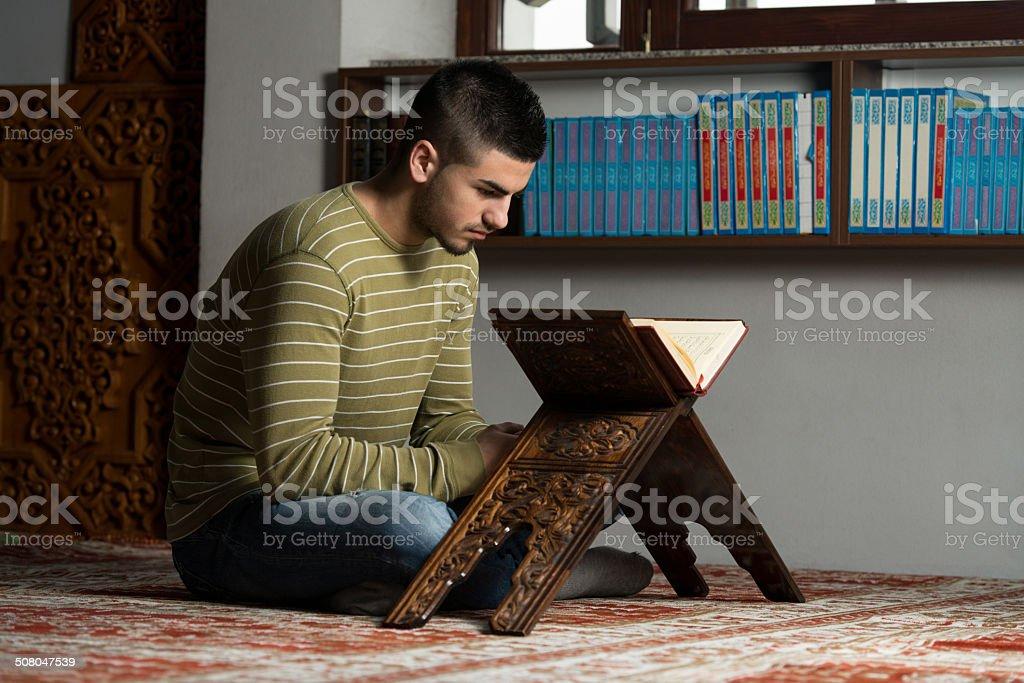 Young Muslim Guy Reading The Koran stock photo
