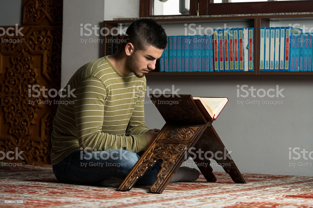 Young Muslim Guy Reading The Koran stock photo