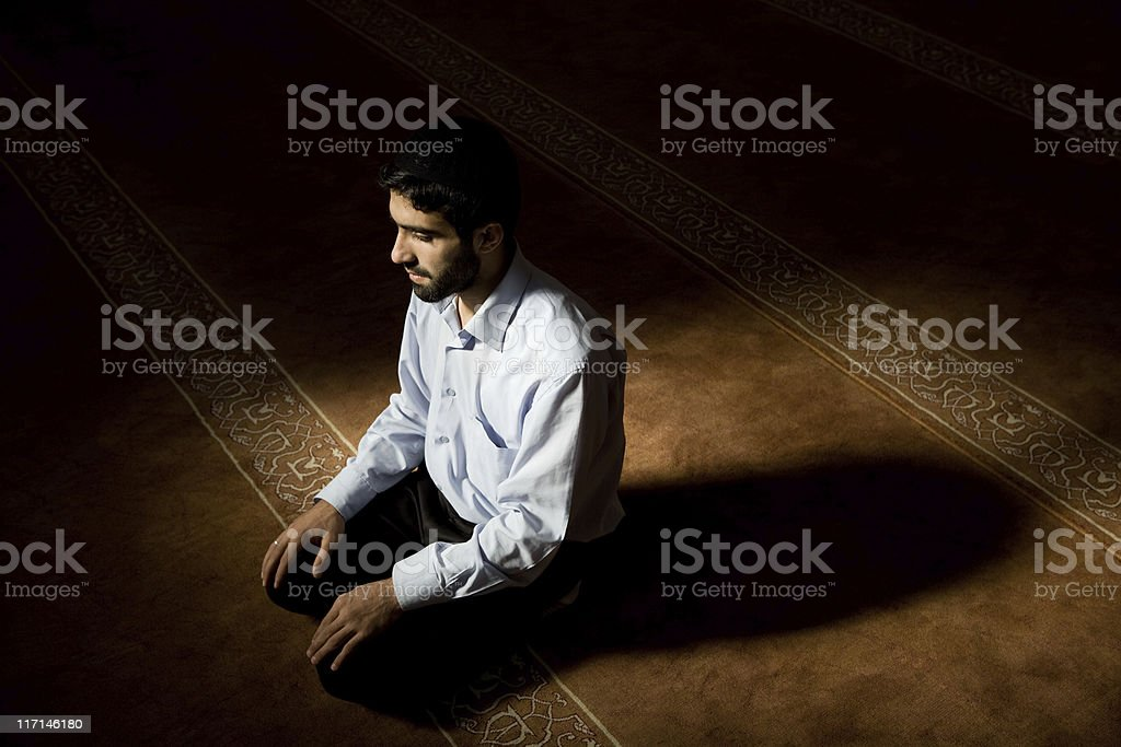 Young muslim man praying in mosque, natural day light stock photo